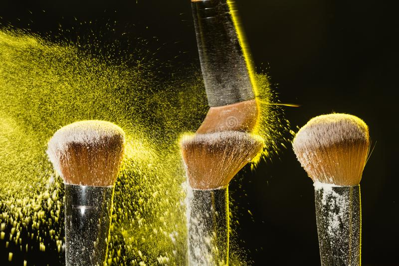 Three brushes for makeup with yellow make-up powder in motion on a black background stock photography