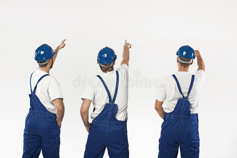 Three builders making a renovation. Three young builders making a renovation royalty free stock photography