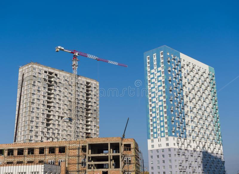 Three buildings of varying degrees of readiness are being built. A new high-rise tower crane is working royalty free stock image