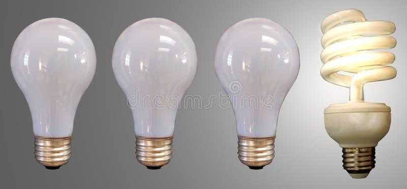 Three Bulbs and a Fluorescent. Three incandescent light bulbs with a lit fluorescent bulb stock photo