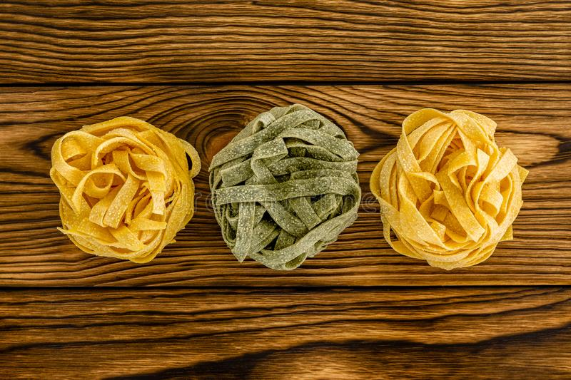 Three bundles of wheat pasta on wood table stock photography