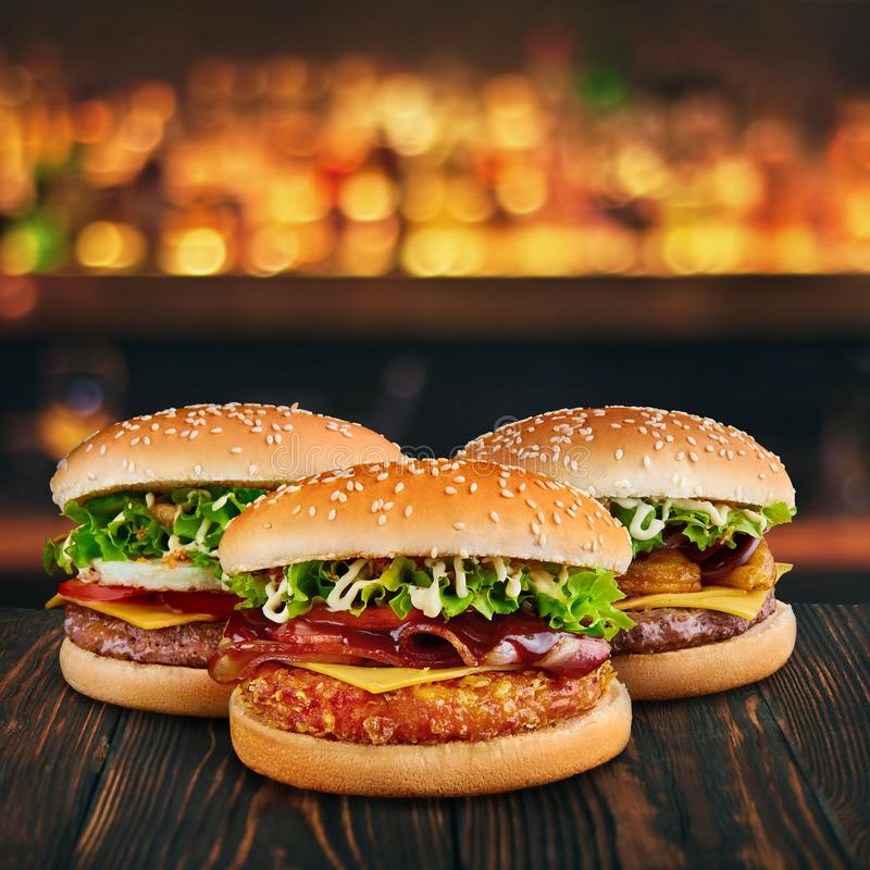 Three burgers at brown wooden tabletop with blurred bar at backdrop . Fastfood concept with hamburgers at wooden table.  stock photography