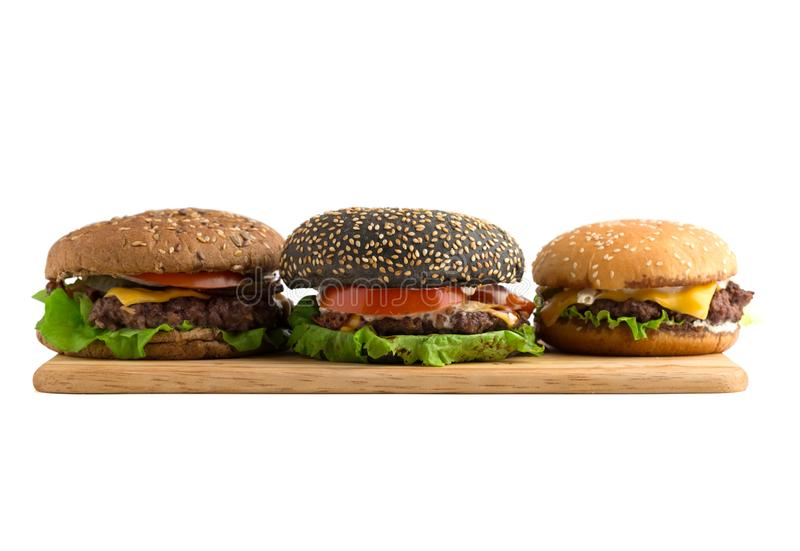 Three burgers on a wooden board cut out on a white background. Beef patties, cheddar cheese, lettuce, bacon, pickled cucumber, tomato and balsamic burgers. In royalty free stock photography