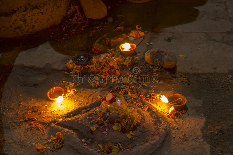 A Three burning candles near the ancient altar with flowers at night time on Diwali royalty free stock photo
