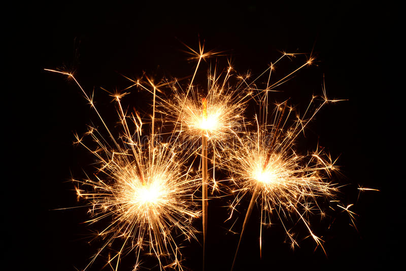 Three burning christmas sparklers. Photo of three burning christmas sparklers on a black background stock photo