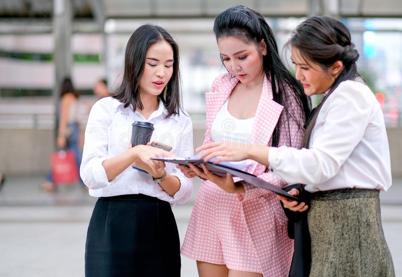 Three business Asian girls discuss together about their works outside the office during day time royalty free stock photos