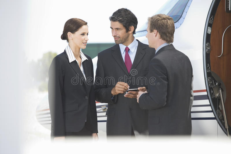 Three business colleagues standing by a plane royalty free stock photo