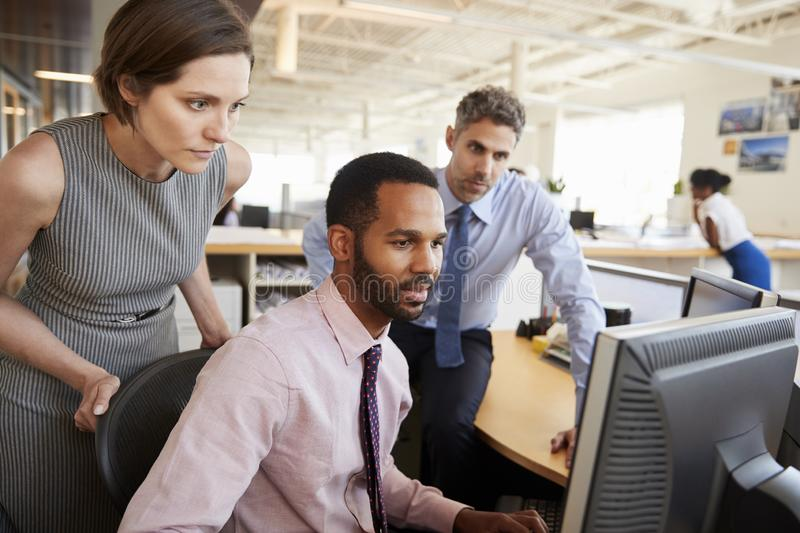 Three business colleagues working together around a monitor royalty free stock image