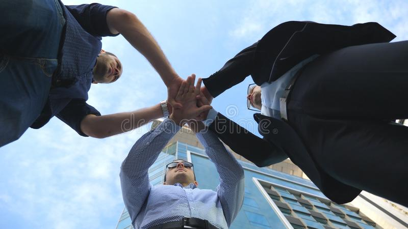 Three business men standing outdoor near office and stacked arm together in unity and teamwork. Hands of businessman stock photo