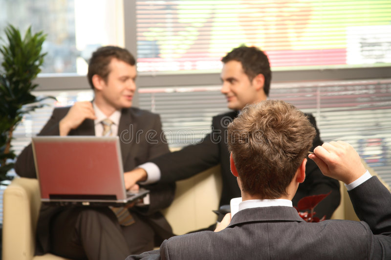 Three Business men working in the office. Three young business men working in the office. One solving problem in focuss stock image