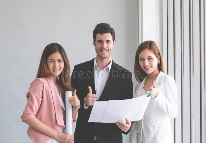 Three business people discussing on Real estate plan looking stock photo