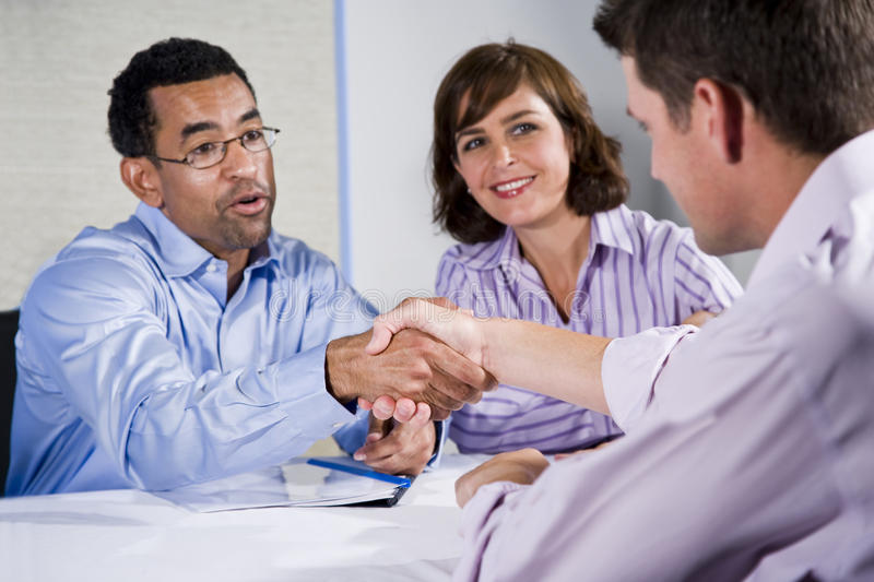 Three business people meeting, men shaking hands. Multiracial business meeting in boardroom, shaking hands. Focus on handshake royalty free stock photos