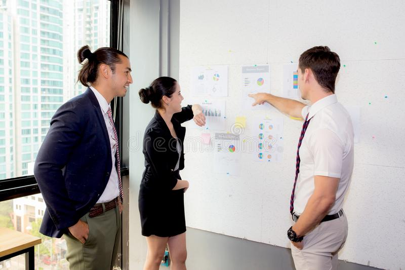 Three business people in modern office looking report and analyzing with talking in meeting room. royalty free stock photos