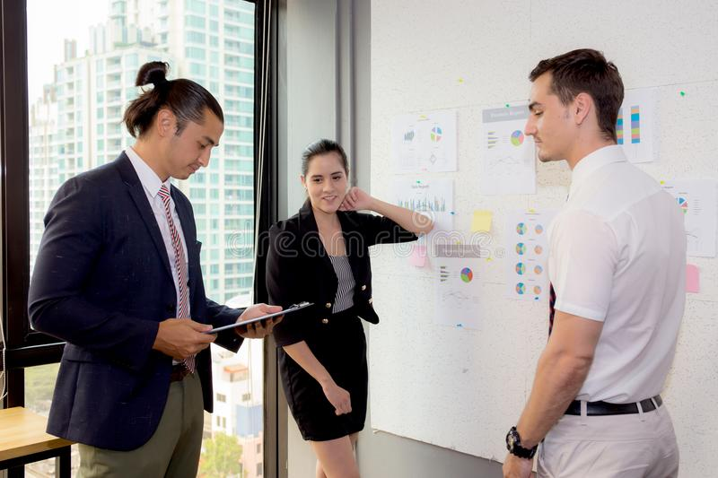 Three business people in modern office looking report and analyzing with talking in meeting room. stock photos