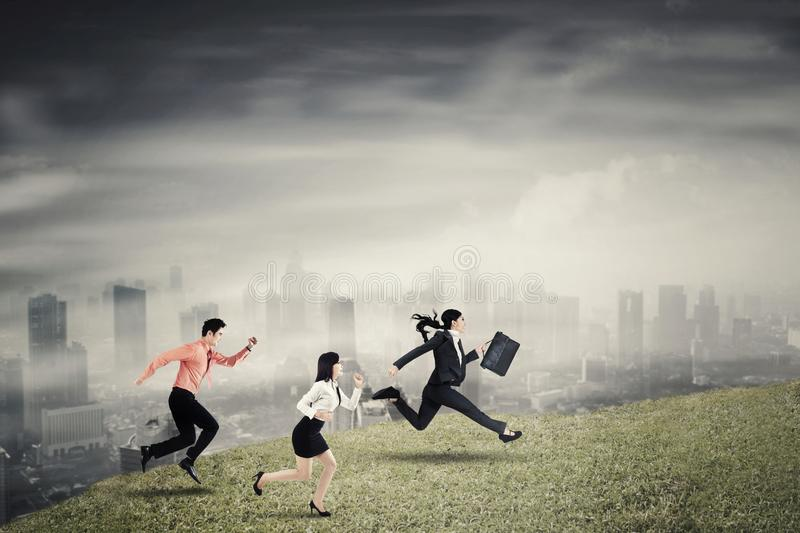 Three business people running speed on the hill. To compete together with cloudy city background stock photos