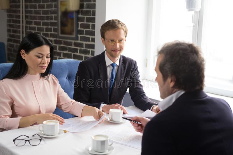 Three business people sign agreement at restaurant stock photo