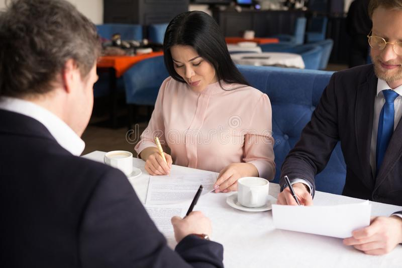 Three business people sign agreement at restaurant royalty free stock photos