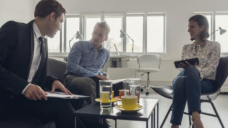 Three business people sitting around a coffee table stock photo