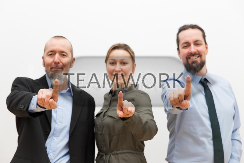 Three business people touching a virtual button. Three business people, two men and one women are touching a virtual button on a touchscreen with the word royalty free stock photo