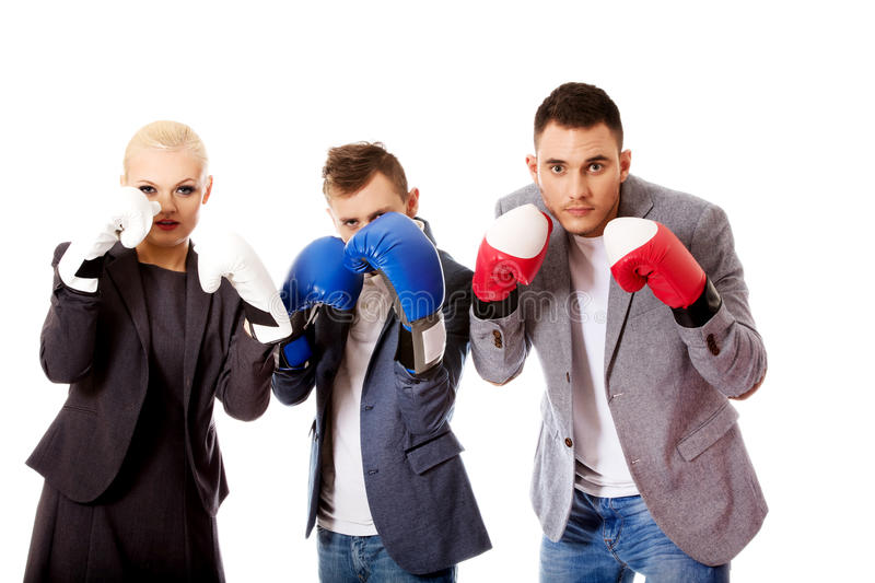 Three business people wearing boxing gloves stock image