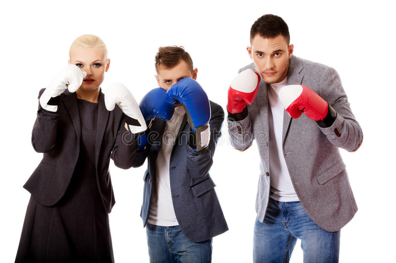 Three business people wearing boxing gloves royalty free stock image
