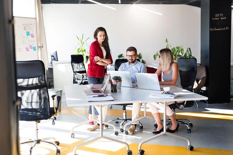 Three business people in the office talking together. Three business people in the workplace. Two women and men talking together in the office royalty free stock image