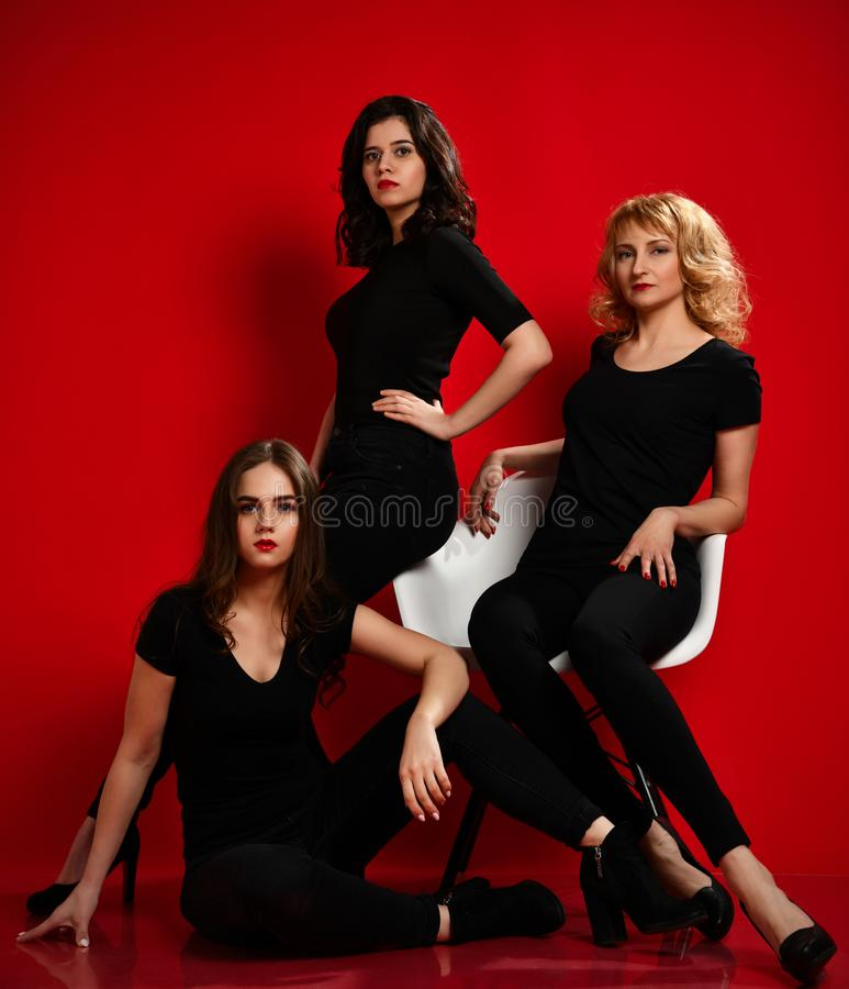 Three business woman in black dresses having fun celebrating on red stock image