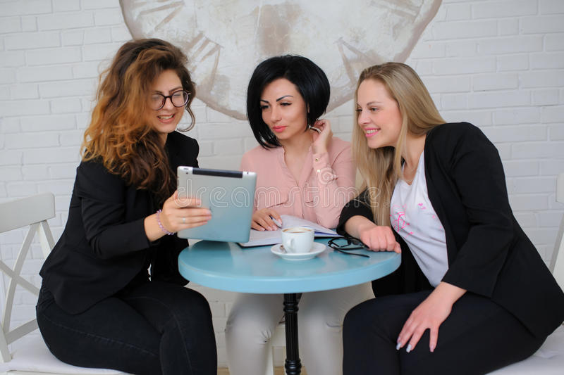 Three business women have a meeting. In a vintage cafe/office and working on a notebook portable compute royalty free stock photos