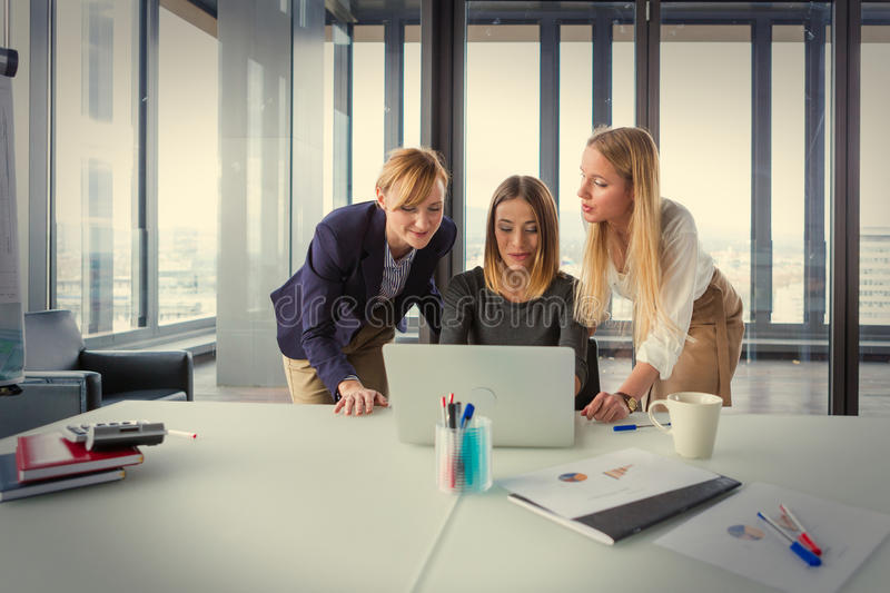 Three business women in modern office working on the project together. Post processed with vintage film filter royalty free stock photo
