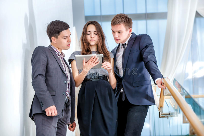Three businessman standing on the stairs solve business problems. Several young people are at each other and smiling. People hold a tablet in the hands royalty free stock photo