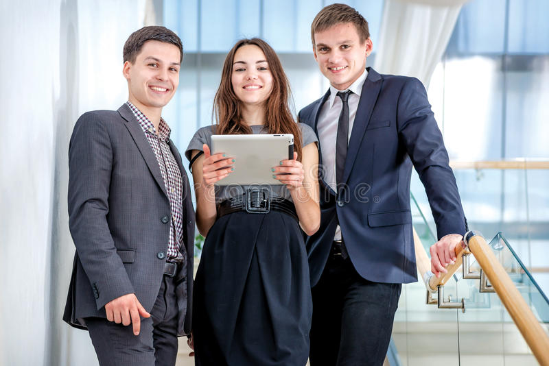 Three businessman standing on the stairs solve business problems. Several young people are at each other and smiling. People hold a tablet in the hands royalty free stock image
