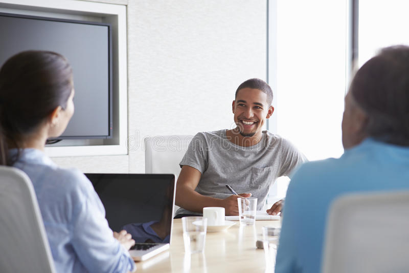 Three Businesspeople Having Meeting In Boardroom royalty free stock images