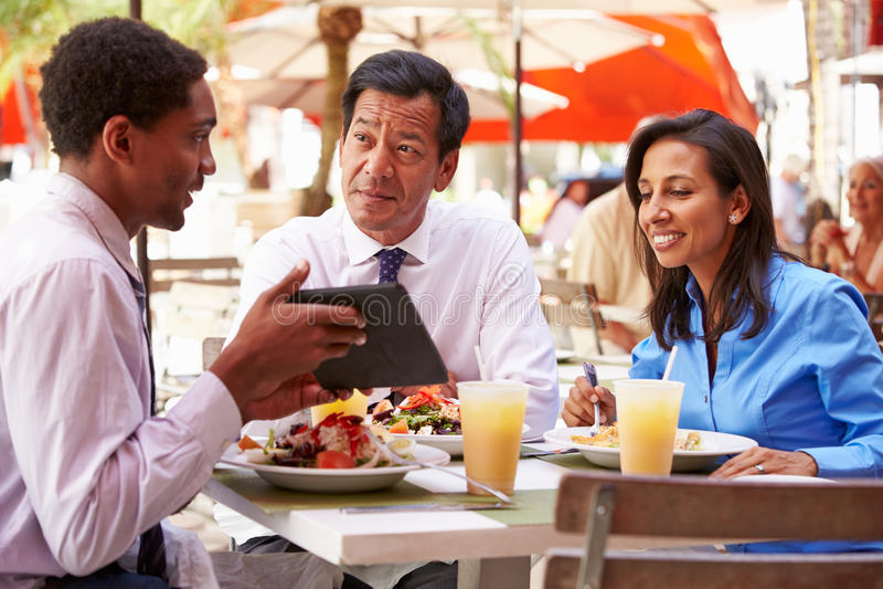 Three Businesspeople Having Meeting In Outdoor Restaurant stock photos
