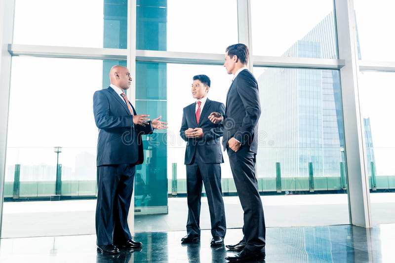 Three businesspeople standing in office lobby royalty free stock photography