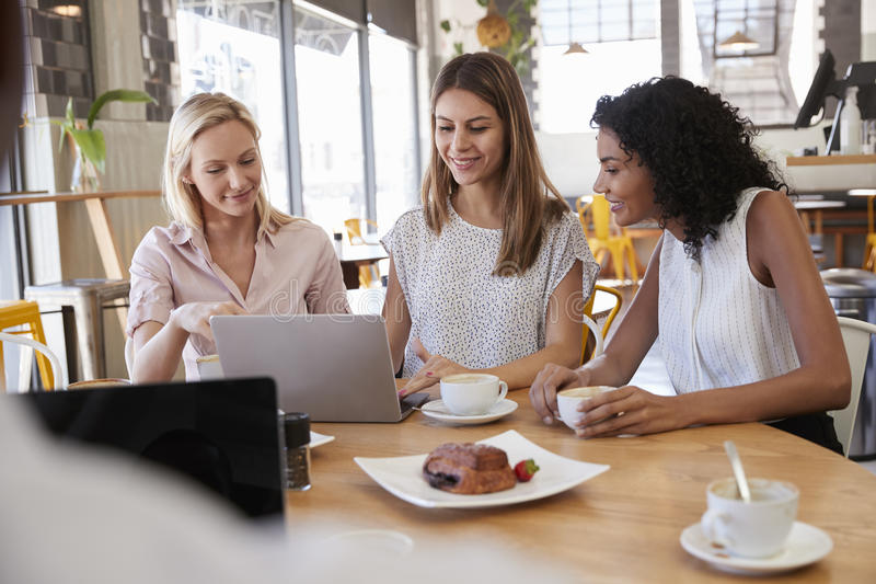 Three Businesswomen Having Meeting In Coffee Shop royalty free stock image