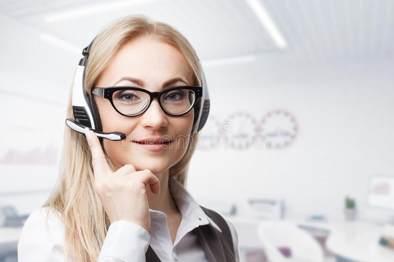 Three call center service operators at work. Portrait of smiling pretty female helpdesk employee with headset at workplace stock photography