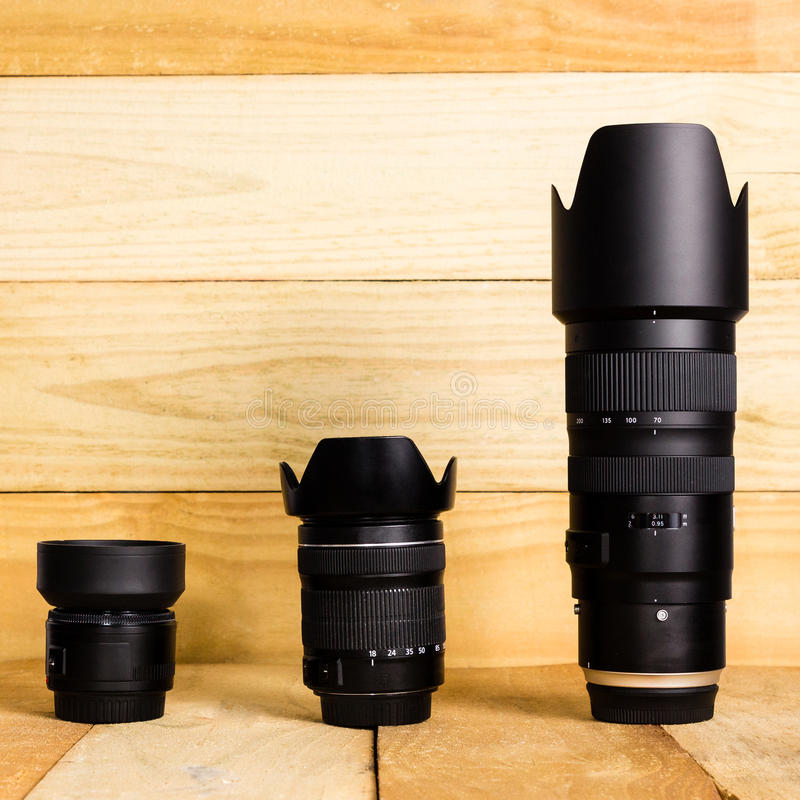 Three Camera Lenses with Lens Hoods Against a Wooden Background royalty free stock photo