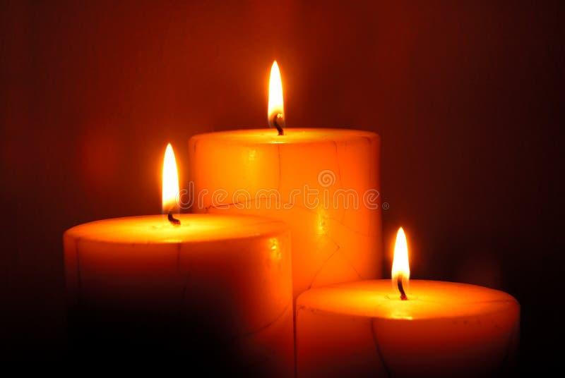Three candles. Illuminating a dark room