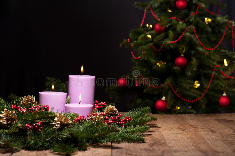 Three candles in an advent flower arrangement. For advent and Christmas, with a christmas tree royalty free stock images