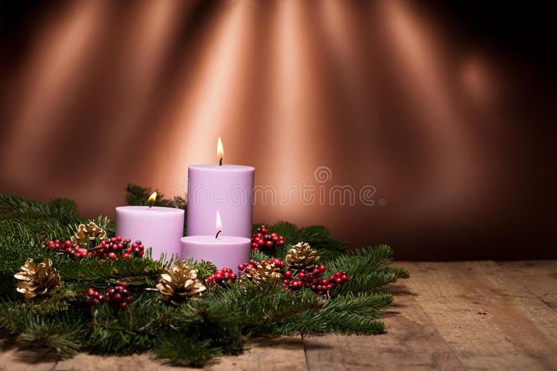 Three candles in an advent flower arrangement. For advent and Christmas on a wooden surface royalty free stock image