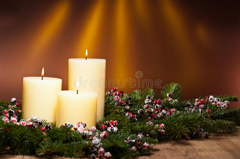 Three candles in an advent flower arrangement. For advent and Christmas on a wooden surface stock image