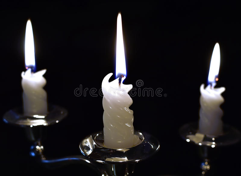 Three candles that burn with a beautiful and atmospheric flame in the darkness stock images