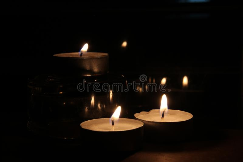 Three candles in the dark stock photography