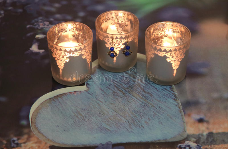 Three candles in a glass and earrings royalty free stock image