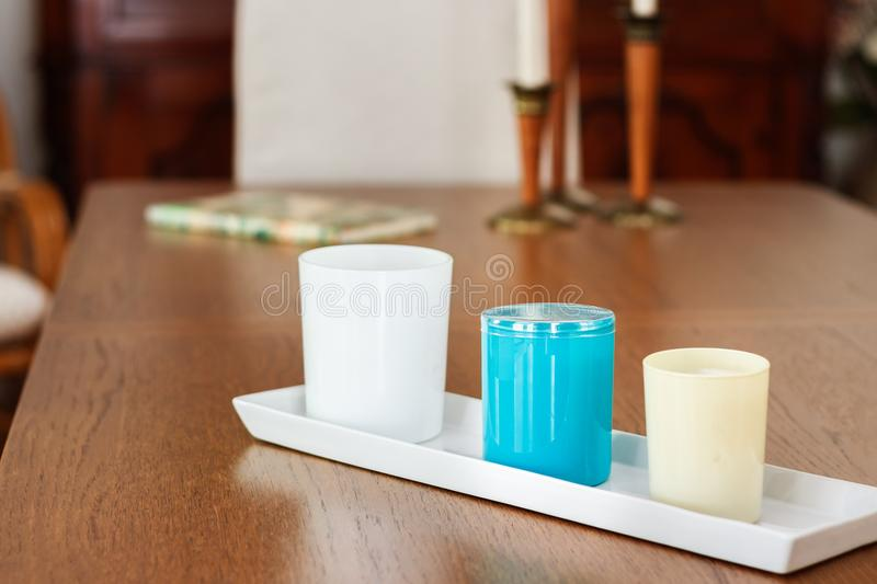 Three candles with perfum on a dinning table. Three candles with perfum in different sizes placed on a dinning wooden table, interior, natural light stock image