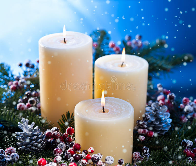 Three candles with snowfall