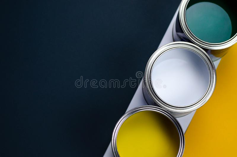 Three cans of multicolored paint on a gray-orange with a white background royalty free stock photo