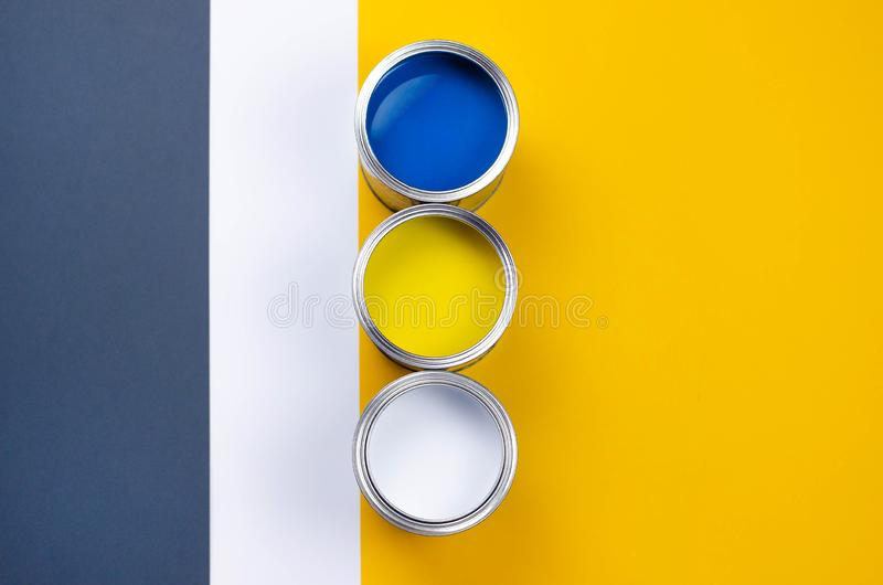 Three cans of multicolored paint on a gray-orange with a white background stock photography