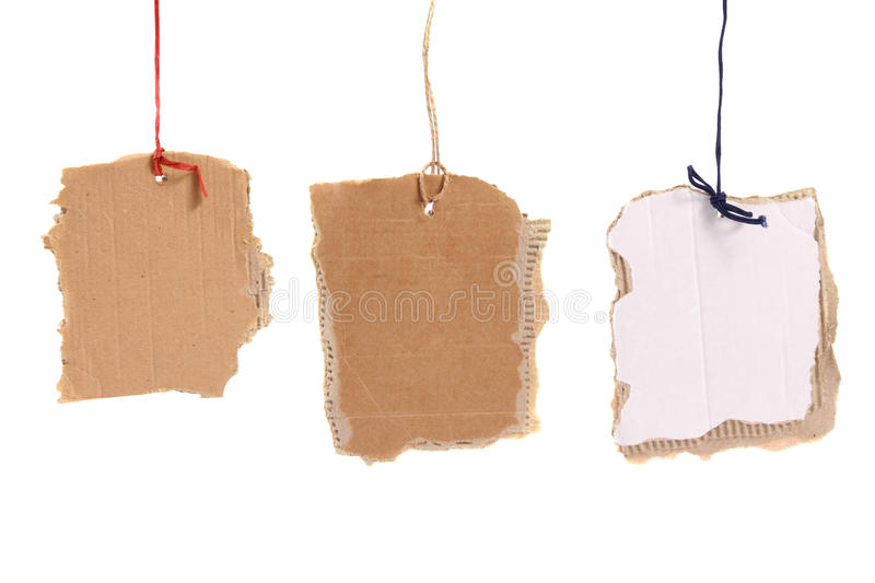 Three cardboard tags hanging on white background. Three different cardboard tags hanging on white background royalty free stock images