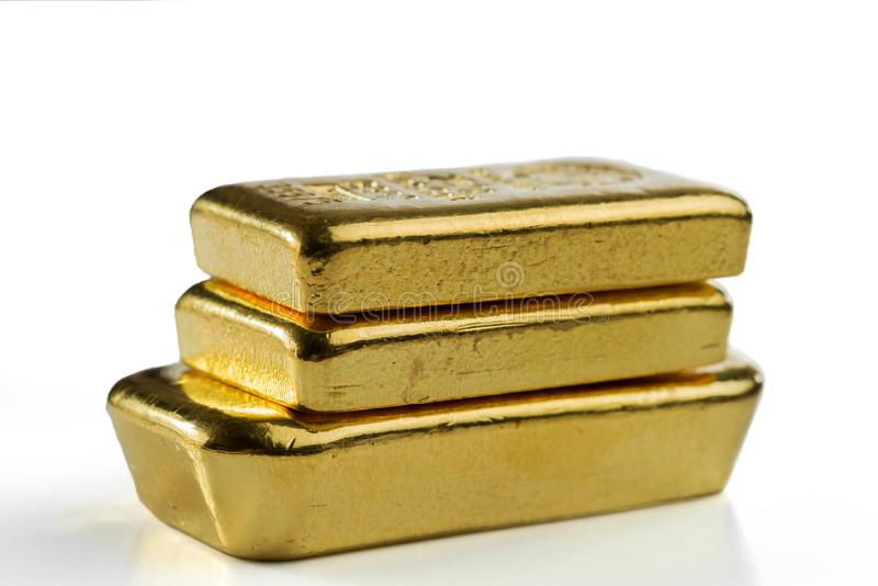 Three cast gold bars are in a pile. Isolated on a white background stock photography